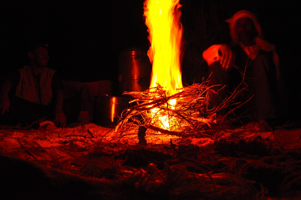 A Bedouin sits next a brightly burning fire in the Sahara desert