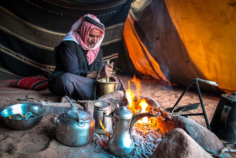 Jordanian Bedouin man grinding coffee near a fire