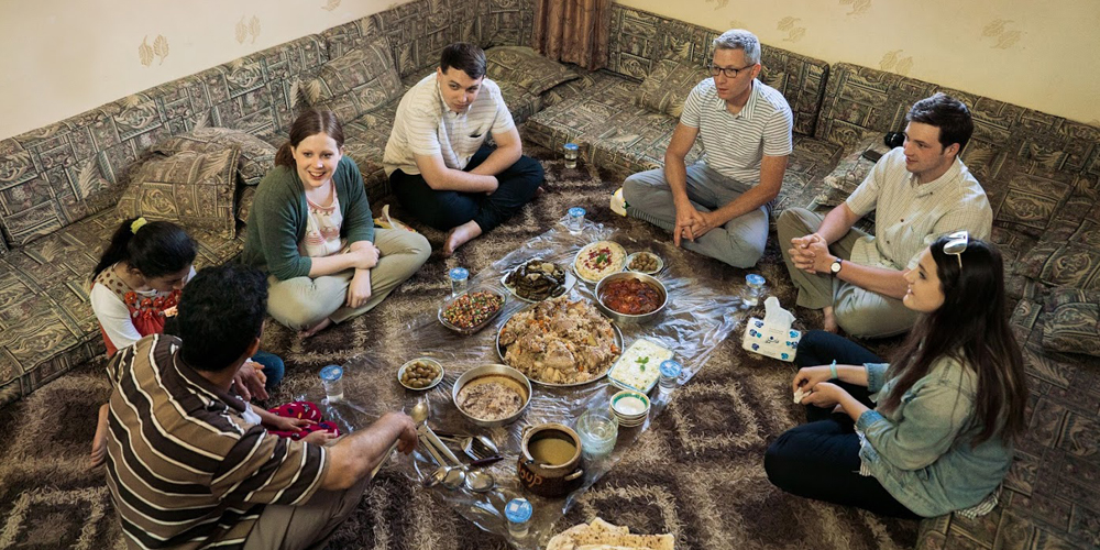 Travelers enjoy a meal with a local family in Orjan, Jordan