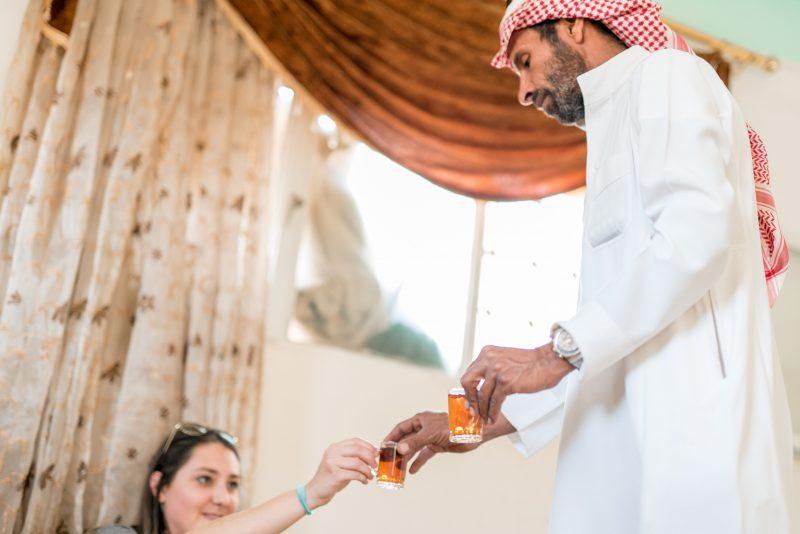 Bedouin man serving tea to a woman on a Jordan tour in Wadi Rum