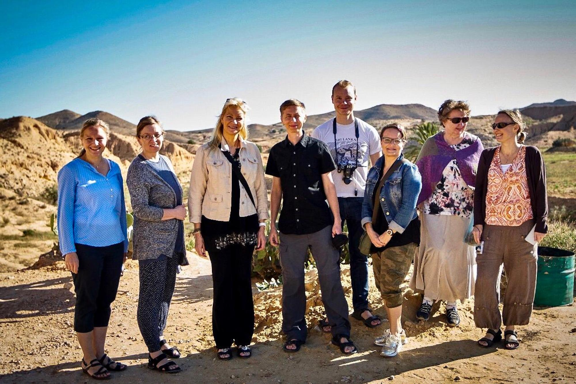 Group of travelers posing in Matmata Tunisia with desert landscape in the background