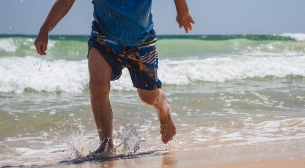 Boy running along the shoreline